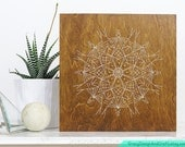 """Mandala Geometric Snowflake Stitched on 12"""" x 12"""" Wood Panel. White thread with gold beads. Light wood. Holiday home, room and office decor"""