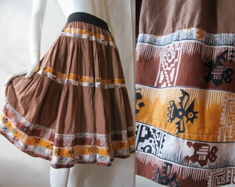 1950's squaw skirt in milk chocolate brown with orange, black, and white Navajo print stripes, about a medium
