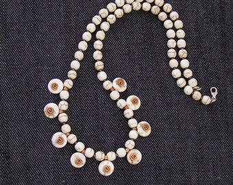 Beige gemstone necklace with copper spirals