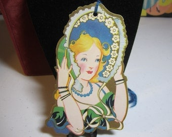 Art Deco 1930's unused die cut gold gilded gorgeous bridge tally card pretty lady in large green and blue bonnet matching dress
