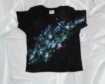 Sprawling galaxy of sparkling blue and green hand painted on a black cotton, Rabbit Skins 18 month T