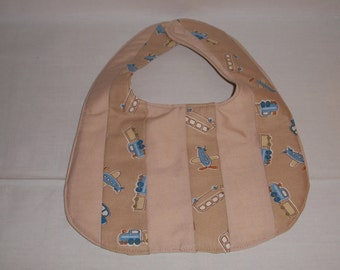 Bib. quilted tan transportation theme bib.