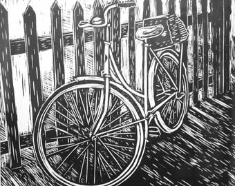 Linocut print of a bike against a fence