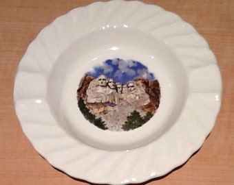Vintage collectible souvenir ashtray from Mount Rushmore, South Dakota. Has a beautiful graphic of the monument and a cool scalloped edge.