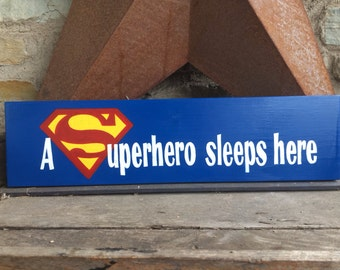 A Superhero sleeps here wooden sign