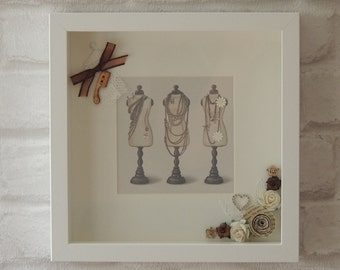 Shadow box frame with decorated manikins image.
