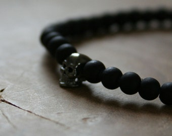 Black Skull: an elastic beaded bracelet with gunmetal skull and matte black glass beads.
