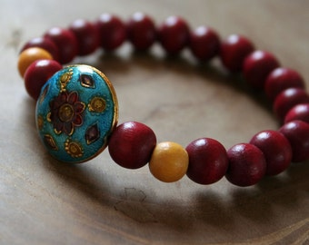 Summernight: an elastic beaded bracelet with red and yellow wooden beads and cloisonne enamel bead in blue, red and yellow