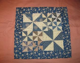 Mini pinwheel quilt of blues, almond, tan andpink