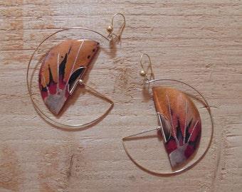 Copper colored earrings in focus