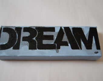 acrylic painting, 12 inches w by 4 inches h, stenciled with the word DREAM