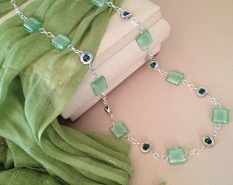 This stunning pale green glass beaded necklace has chunky silver links with embedded emerald glass stones.