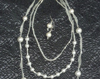 Multistrand pearl necklace on a silver mesh ribbon with matching earrings