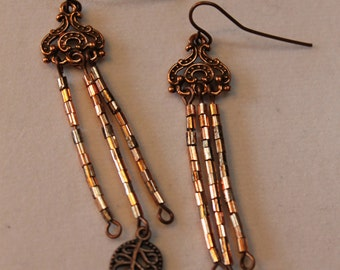 Copper chandelier earrings with glass bead tassels and single centered leaf