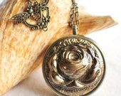 Music box locket,  round locket with music box inside, in bronze with rose on front cover.