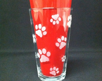 Tumbler glass etched with paw print design.  Clear glass, frosted (sandblasted) design, 16 ounce capacity.
