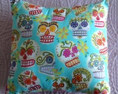 Square cushion cover in Alexander Henry's blue Sugar Skulls glitter print teamed with striped back