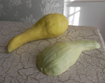 one whole porcelain yellow crookneck squash sculpture, and one half