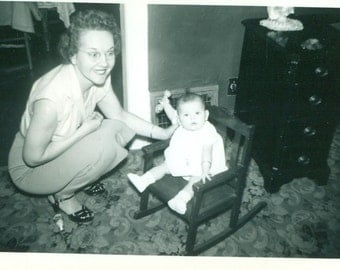 Baby Girl Sitting in Rocking Chair Holding Rattle Mother Helping 1940s Vintage Black White Photo Photograph