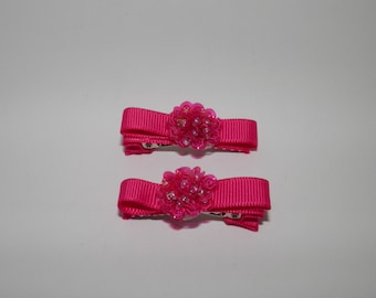 Hot pink hair clip with flower on partially lined alligator clip with teeth.