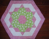 Quilted Easter table mat, hexagon shaped with lots of bunnies playing on a field of pink flowers.