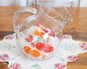 Vintage juice pitcher with orange and red graphics