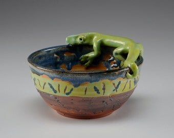 Green lizard resting on rim of  cereal bowl sized blue green earth bowl
