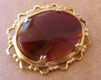 vintage mini brooch of  reddish brown shiny polished stone cabochon in gold tone setting