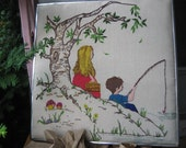 vintage embroidered picture of girl and boy on picnic and the boy is fishing in metal frame 1990's or earlier 20 inches square