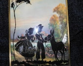 Vintage reverse silhouette painting on convex glass.  1930's,1940's. Two children and donkey.