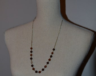 Brown beaded necklace with a clear accent bead
