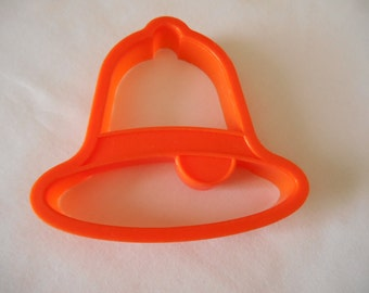 An Orange Bell Shaped Cookie Cutter, 4 1/8 inches by 3 15/16 inches