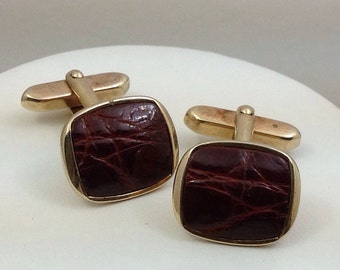 Gold tone cuff links with brown reptile leather inlay.