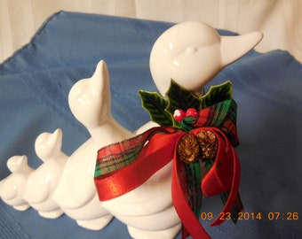 Four geese of ceramic in a row with red and green ribbons on.