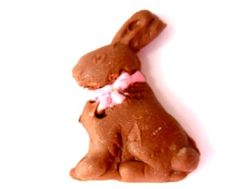 A chocolate bunny with pink ribbon around her neck dollhouse miniature.