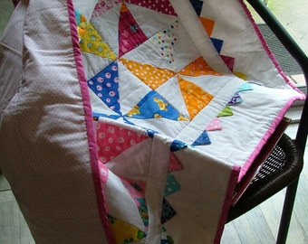 Cot quilt with bright pinwheels and 3D flying geese