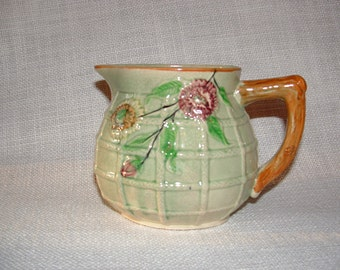 Japanese Majolica pitcher in a pretty vintage green with brown tree branch handle was made around 1940..