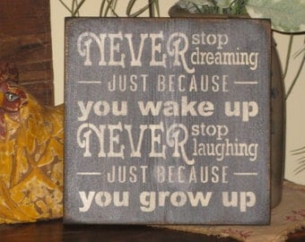 Inspirational, motivational primitive rustic sign Never Stop Dreaming Just Because You Wake Up. Never Stop Laughing Just Because You Grow Up
