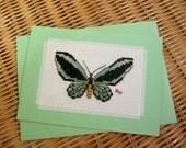 Hand cross stitched Australian native card - Cairns Birdwing Butterfly.  Green coloured card with matching envelope and  white paper insert.