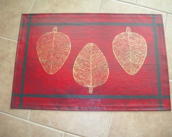 Hand painted, gold/red/black floor cloth.
