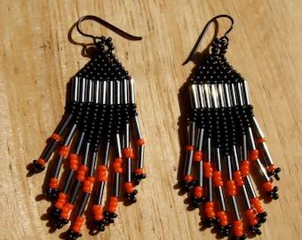Black, hematite, and orange dangly beaded earrings with grey niobium earwires