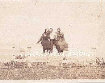 Vintage Real Photo Postcard - Cute Photo of a Man with Two Women Sitting on a Fence