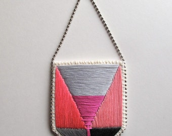 Geometric pendant necklace with color block design hand embroidered in pinks and grays with silver ball chain