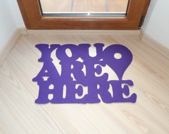 "Doormat ""You are here"" with Google maps pin. Custom door mat message in red."