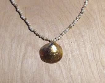 Gold Finish Clam Shell on Sand and Gold Colored Bead Necklace