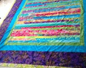 Finished queen quilt, mostly Batik with a purple print backing.