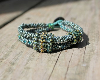 Kumihimo sage green bracelet with beaded beads and carved button clasp