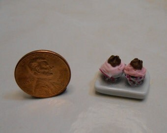 Miniature Valentine pair of pink iced cupcakes with chocolate kisses on top