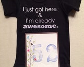 DISCOUNTED -- Nearly Perfect -- #52b, see photos -- I just got here & I'm already awesome.  -- black snapsuit, size 0-3 months