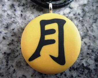 MOON Japanese kanji symbol hand carved on a polymer clay yellow pearl color background. Pendant comes with a FREE necklace